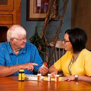 A nurse chats with a patient in his home about his medications.